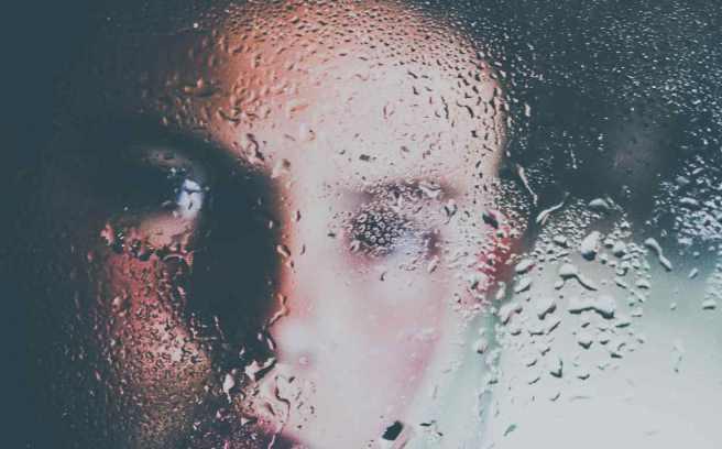 traumatisme crânien femme derrière une vitre sous la pluie